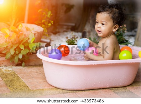 Asian baby Bathing in tubs and Asian baby enjoyed playing with colored balls. - Sunlight filter effect.  - stock photo