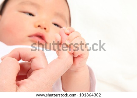 Asian baby boy holding a finger to his mother - stock photo