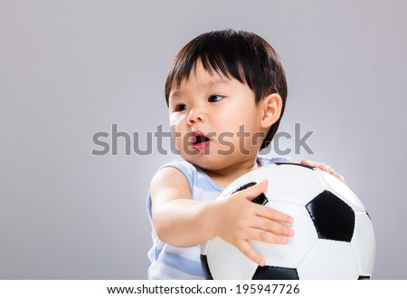 Asian baby boy holding soccer ball - stock photo