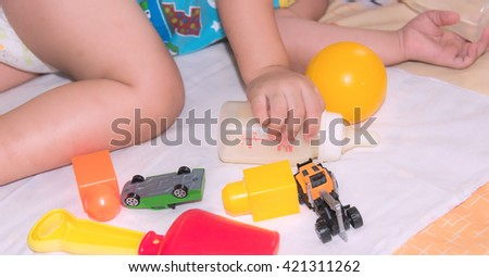 Asian baby boy laying on bed with his toy while drinking water from milk bottle - stock photo