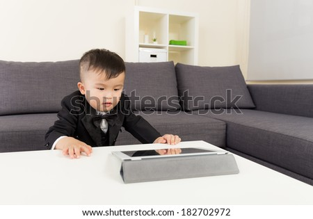 Asian baby boy watching on tablet - stock photo
