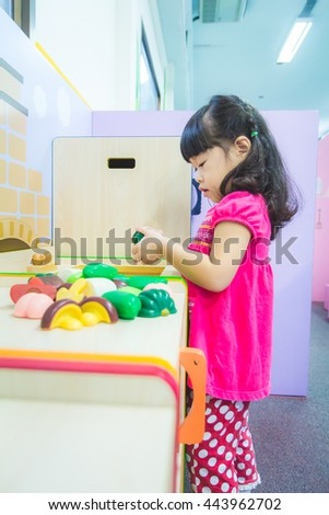 Asian baby cute girl with curly hair in the kitchen toy