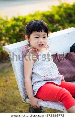 Asian baby cute girl with curly hair sit on the chair
