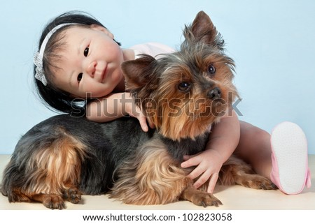 Asian Baby Doll Embracing her pet dog yorkshire sitting down in front on a white background.