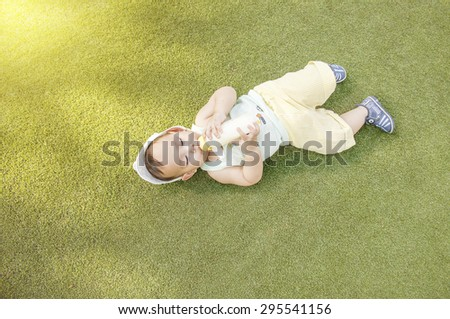 Asian baby drinking milk from bottle while he's laying on the green grass field at the outdoor park - stock photo