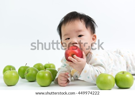 Asian baby eating red apple on white background