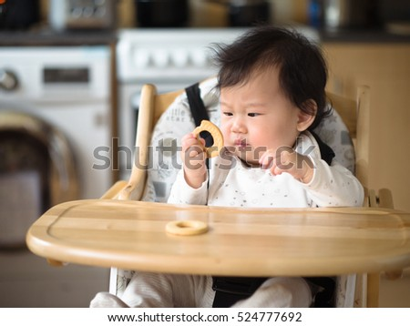 Asian baby girl eating finger food first time