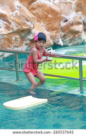 Asian baby girl playing in swimming pool