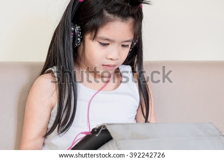 Asian baby girl playing tablet pc with earphone - stock photo