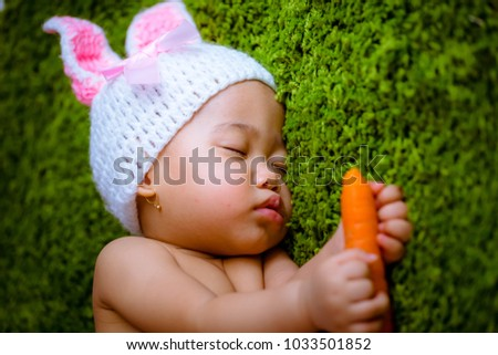 Asian baby girl pose as a bunny on the grass with a carrot