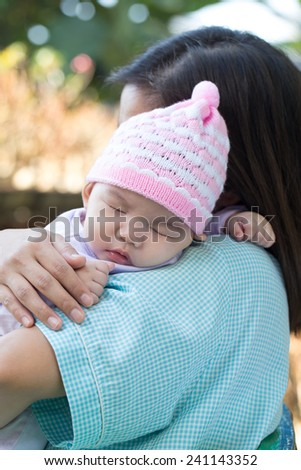 Asian baby girl sleeping on her mother shoulder