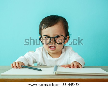 Asian baby girl smiling wearing glasses, on the table (soft focus on the eyes)