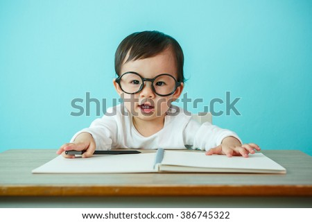 Asian baby girl smiling wearing glasses, on the table (soft focus on the eyes) - stock photo