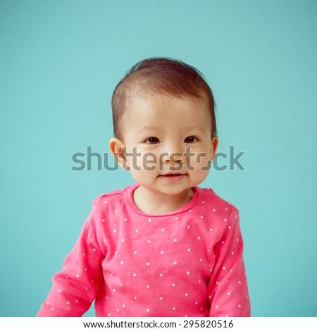 Asian baby girl wearing pink clothing - stock photo