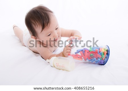 Asian baby happy lying on white bed - stock photo