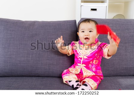 Asian baby holding red pocket with traditional chinese clothing - stock photo