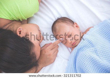 Asian baby sleeping with woman touching her forehead, admiring - stock photo