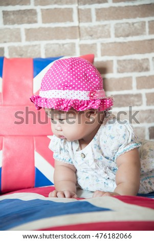 Asian baby wearing a pink hat.