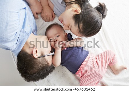 Asian baby with parents, Lying in bed comfortable