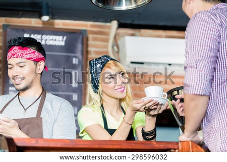 Asian Barista offering cafe to customer in coffee shop, another service worker preparing a drink - stock photo