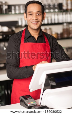 Asian barista staff at the cash counter confirming order. - stock photo