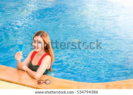 Asian beautiful woman is smiling with cocktail drink in swimming pool