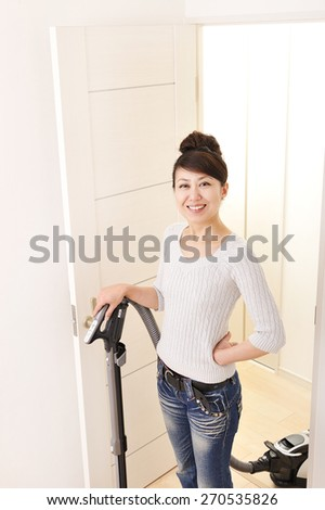 Asian beautiful young woman who wears a vacuum cleaner with a smile - stock photo