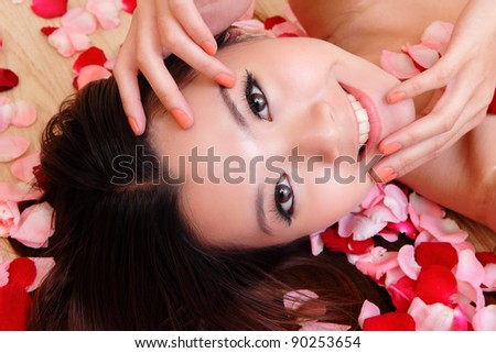 Asian beauty Girl smiling close-up with rose background, Beautiful young woman touching her face looking to the side - stock photo