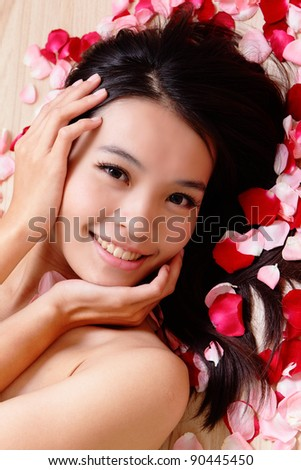 Asian beauty Girl smiling close-up with rose background, Beautiful young woman touching her face looking to the camera - stock photo