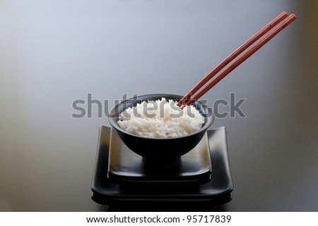 Asian black dishes and bowl with rice and red sticks - stock photo