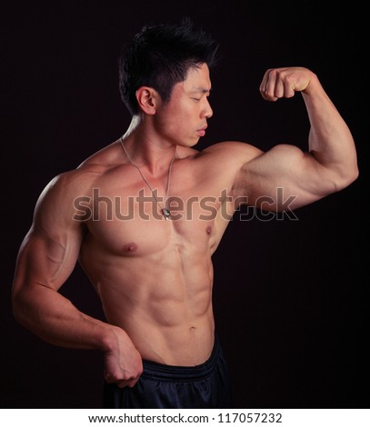 Asian Body Builder flexing left bicep showing off his abs - stock photo