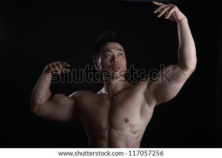 Asian Body Builder waist up posing on black background - stock photo