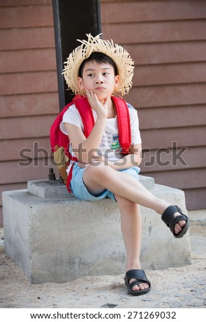 Asian bored child with red backpack is thinking while  - stock photo