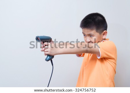 Asian boy aim a fake gun made with barcode scanner, studio shot, on gray wall background with soft shadow