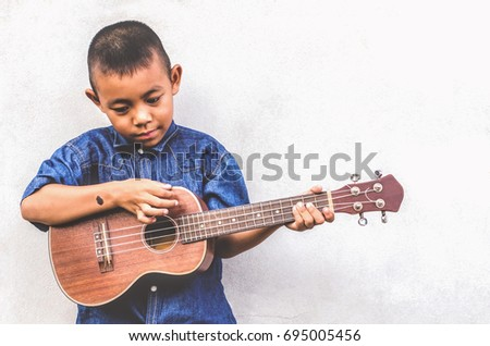 Asian boy Black birthmarks on hand Wearing shirt fashion Jeans Play ukulele cool gesture Passionate love music empty space Old cement wall Child Development Concept Grandson name Promphum