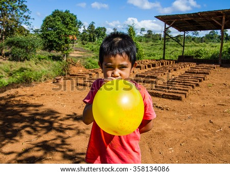 Asian boy blowing up the balloon on dry earthen brick background. - stock photo