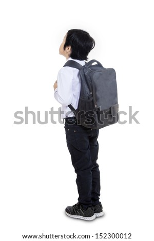 Asian boy carrying backpack, shot from behind isolated on white background - stock photo