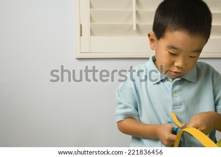 Asian boy cutting paper - stock photo