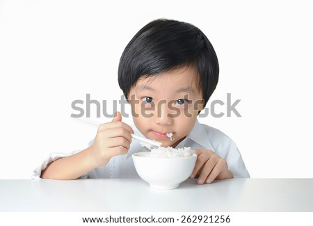 Asian boy eating a bowl of rice with chopsticks - stock photo