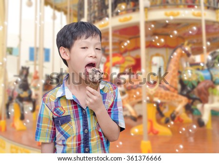 Asian boy eats ice cream in front of merry go round - stock photo