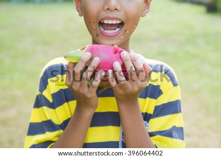 Asian boy enjoy eating exotic Asian Dragon Fruit. - stock photo