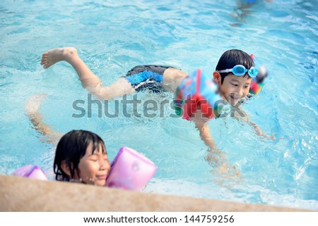 Asian boy enjoying in the pool - stock photo