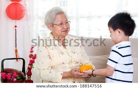 Asian boy giving mandarin oranges to his grandmother  - stock photo