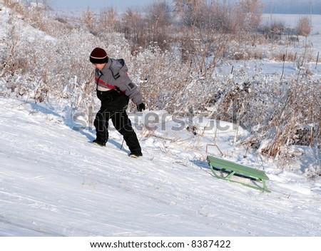 asian boy go uphill in bright winter day - stock photo