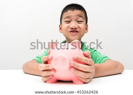 asian boy happy with piggy saving coins - stock photo