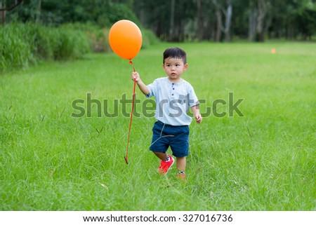 Asian boy hold with orange balloon - stock photo