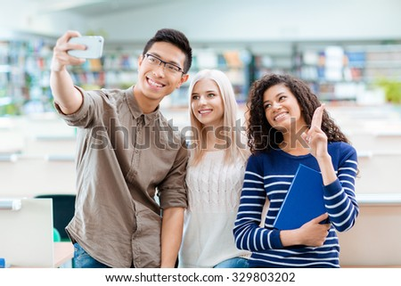 Asian boy in black glasses, blonde beautiful girl and african american curly woman are making selfie using cellphone - stock photo