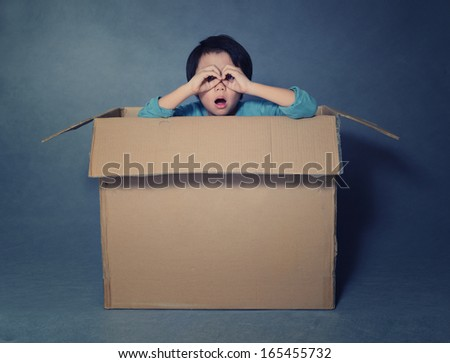 Asian boy in box looking through imaginary binoculars - stock photo