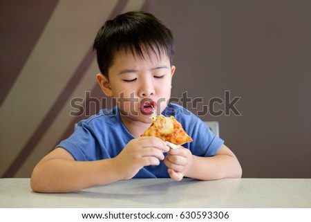 Asian boy is happy to eat pizza with a hot cheese melt stretched on brown background.