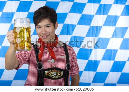 Asian Boy is holding a full Oktoberfest beer stein and smiles happy in camera. In background Bavarian flag visible. - stock photo